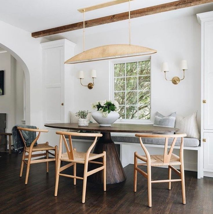 Charming breakfast nook with built in banquette, wishbone chairs, and organic rustic oval wood dining table - Jean Stoffer Design; Kenowa Builder. #breakfastnooks