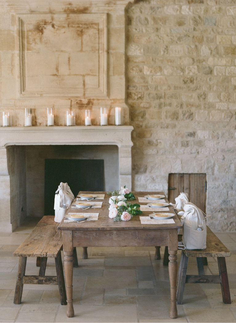 French limestone walls and antique mantel with farm table and benches at Sunstone Winery. #frenchfarmhouse #diningroom #fireplace #rusticdecor #romanticdecor