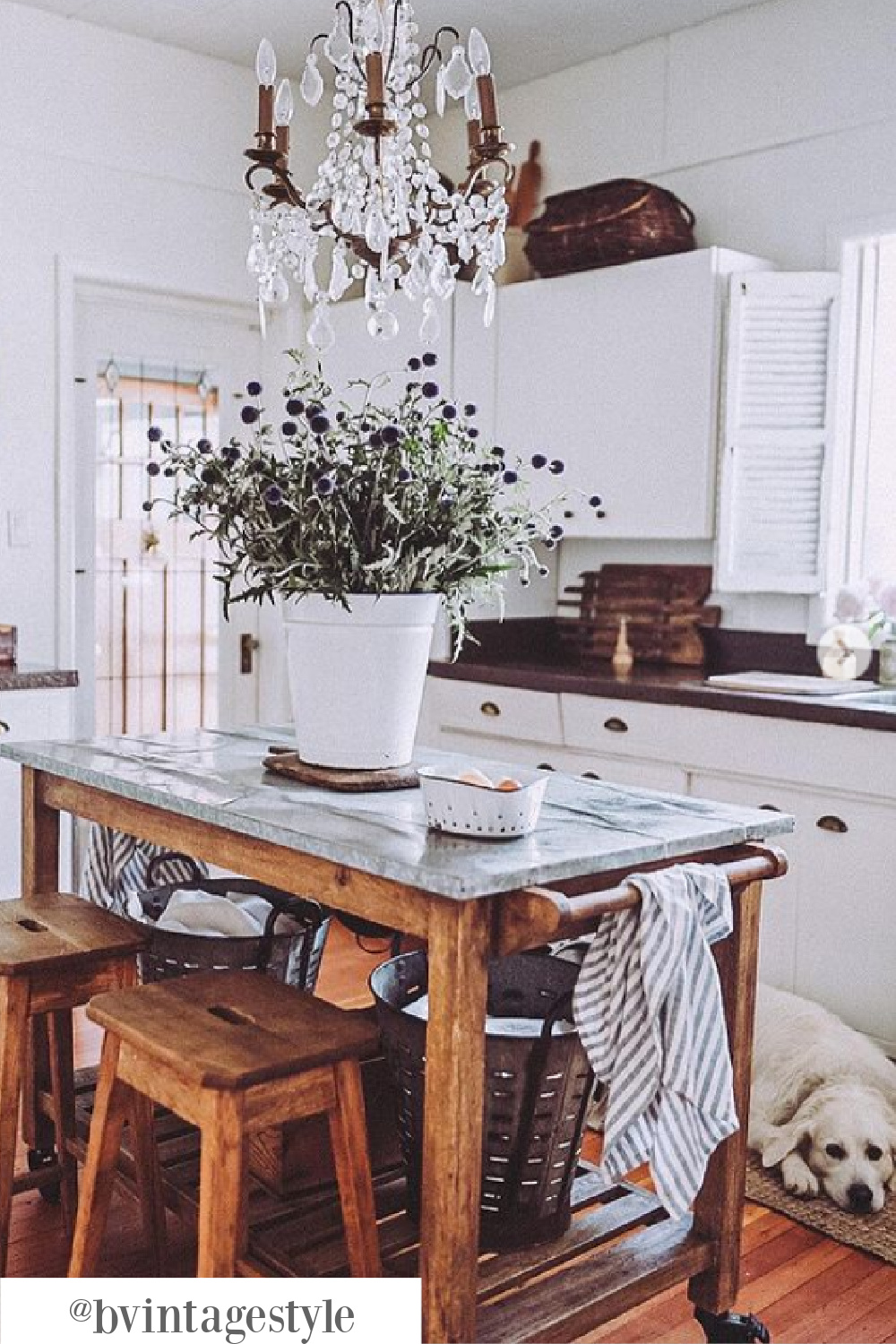 Rustic and charming white farmhouse kitchen with vintage wood work table on wheels - @bvintagestyle. #worktable #kitchencart #vintageworktable