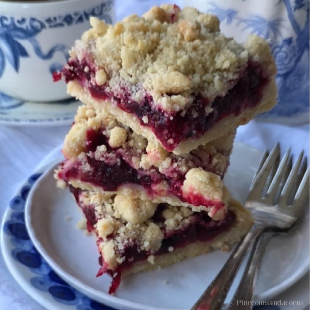 Cranberry crumble bars on blue and white china - Pineconesandacorns. #cranberrybars #fallrecipes