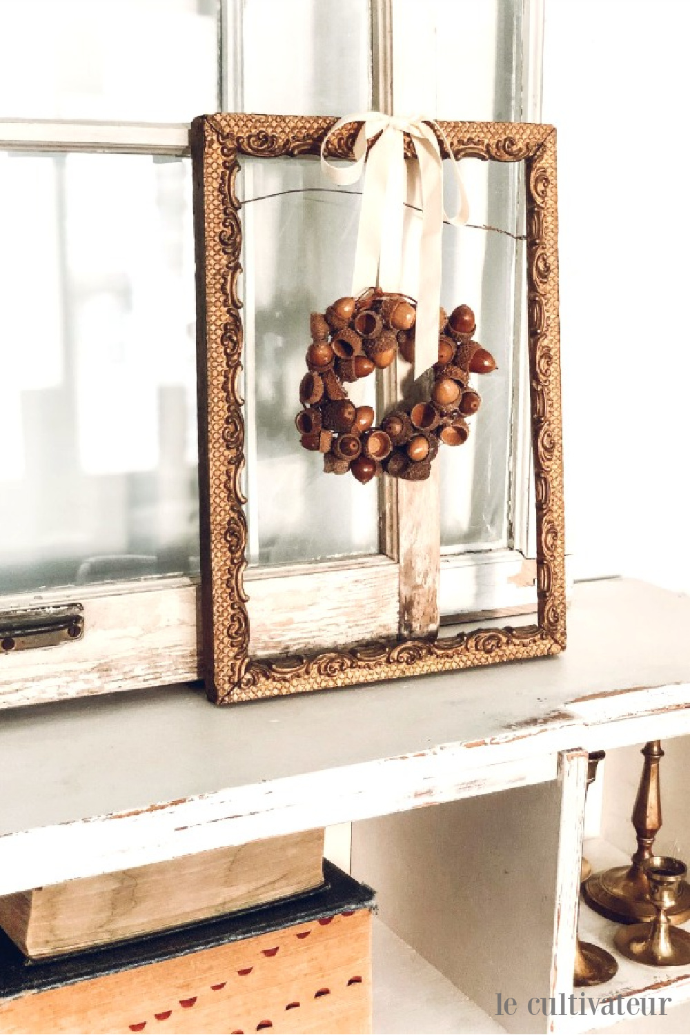 Sweet and rustic acorn wreath hangs on ribbon from vintage frame in a lovely French country white fall vignette - Le Cultivateur. #falldecor #fallwreaths #acornwreath