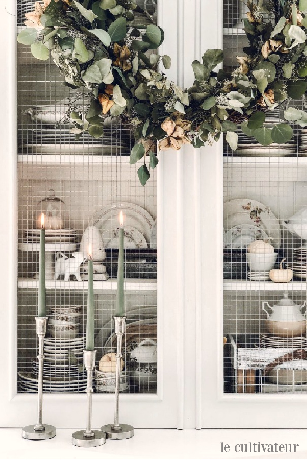 Sage green candles and eucalyptus wreath on a white French country cabinet in a fall vignette - Le Cultivateur. #falldecor #fallwreath #sagegreen