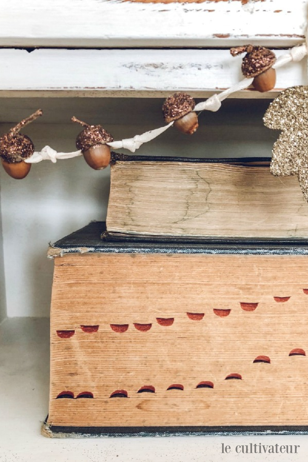 Charming fall acorn garland on a shelf with vintage books sporting aged pages - Le Cultivateur. #acornwreath #falldecor #countrydecor