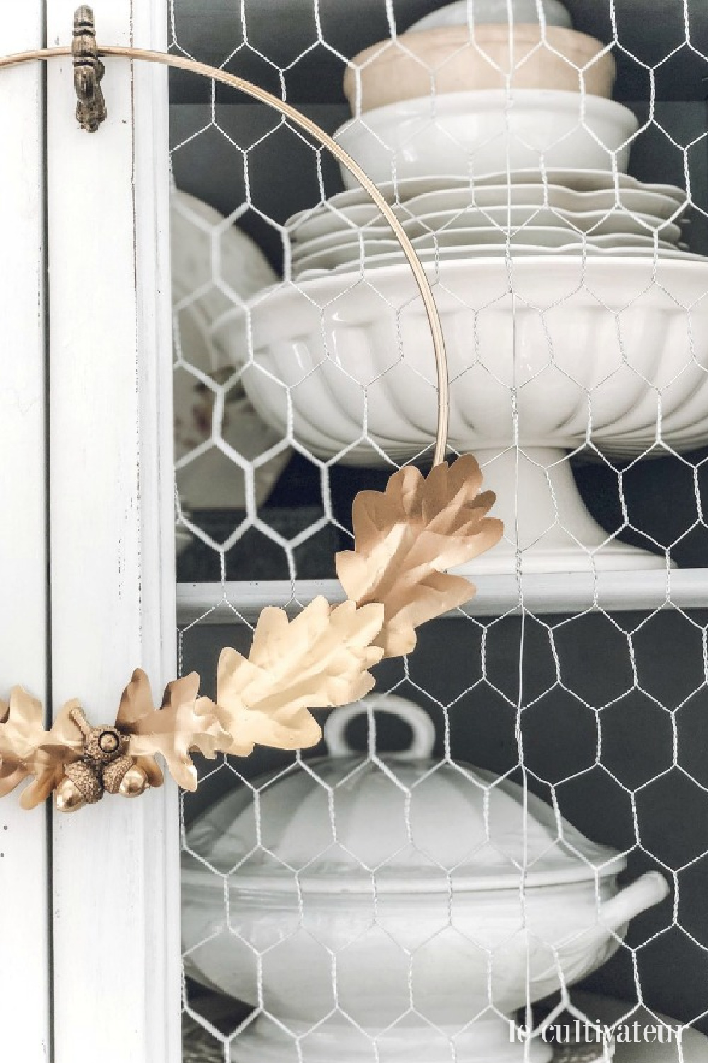 French country fall decor with white ironstone in a country vintage cabinet with chickenwire - Le Cultivateur. #falldecor #frenchcountry #ironstone #chickenwire