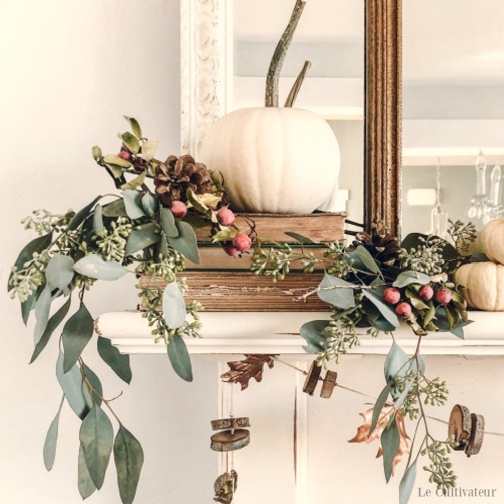 White fall French country pumpkin and acorn decor on a mantel - Le Cultivateur. #frenchcountry #falldecor #fireplacedecor