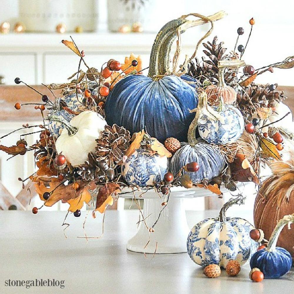 Elegant fall centerpiece with blue and white decoupaged pumpkins and royal blue velvet pumpkins - Stone Gable. Serene French Farmhouse Fall Decor Photos ahead! #centerpiece #fall #pumpkins #tablescape #velvetpumpkins #chinoiserie