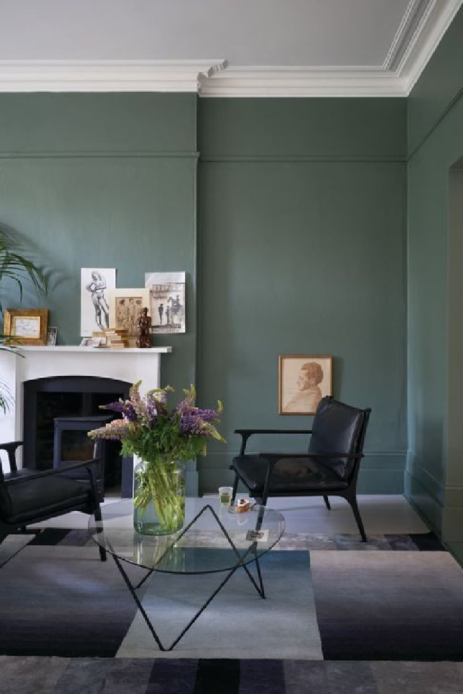 Farrow & Ball Green Smoke painted walls in a living room with European sophisticated style. #farrowandball #greensmoke #paintcolors #deepgreen #moodygreen #greenpaint
