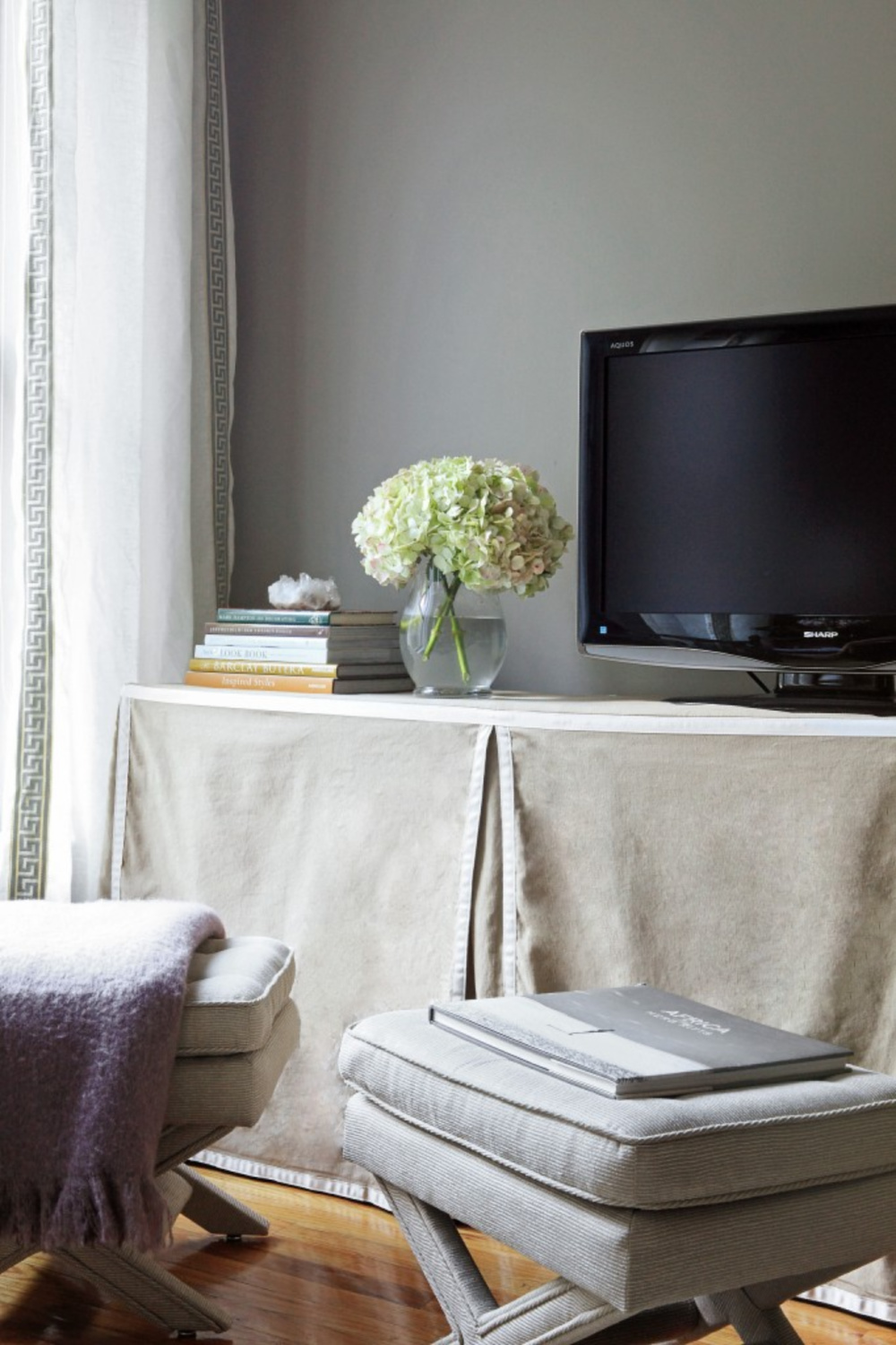 Slipcovered Kallax from Ikea used as a media console for a TV in a neutral space by Nicole Gibbons Style. #kallaxhack #ikeahacks