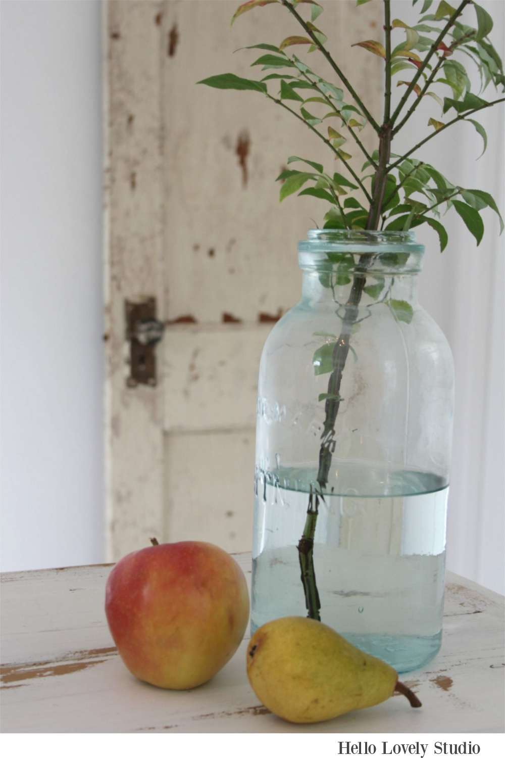 Peaceful, soft farmhouse still life with green mason jar, fruit, and a peely painted door - Hello Lovely Studio.