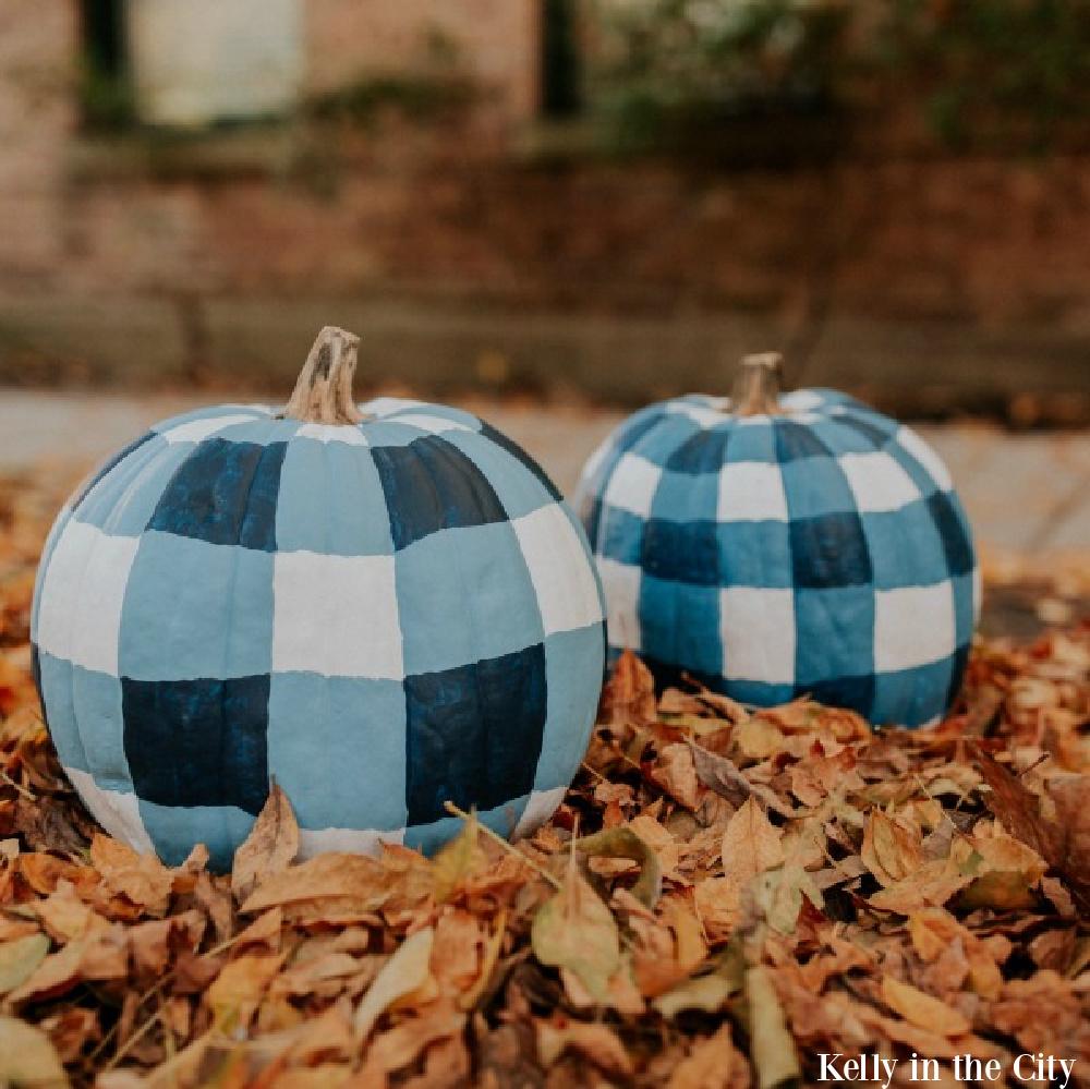 Blue plaid painted pumpkins in orange fallen leaves - Kelly in the City. Serene French Farmhouse Fall Decor Photos ahead! #pumpkins #DIY #plaid #buffalochecks #farmhousedecor