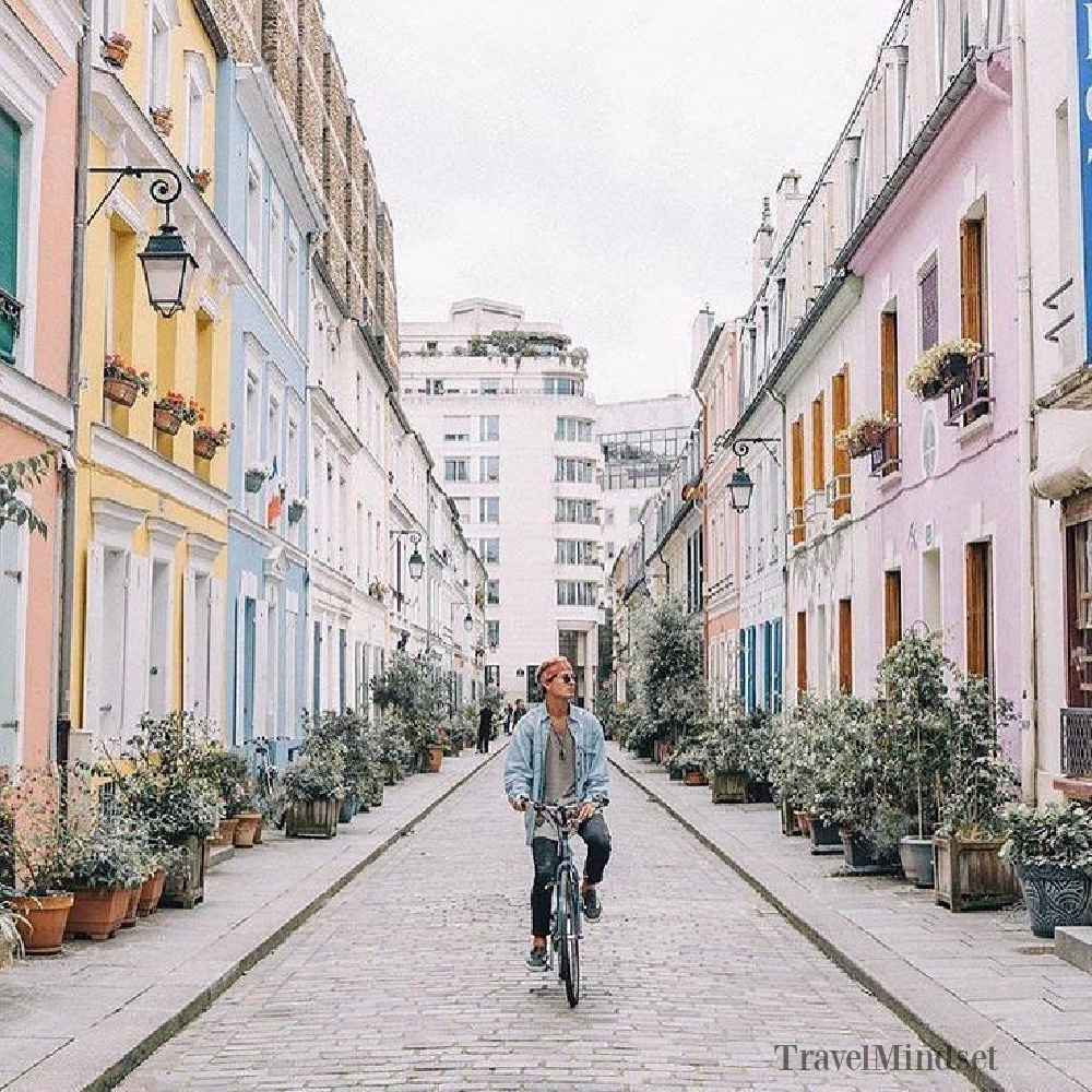 Paris pastels in fall offer a breathtaking design moment with these pretty facades on a street in Paris! @Travelmindset #parisinfall #parispastels #romantichomes #houseexteriors #pastels #autumn