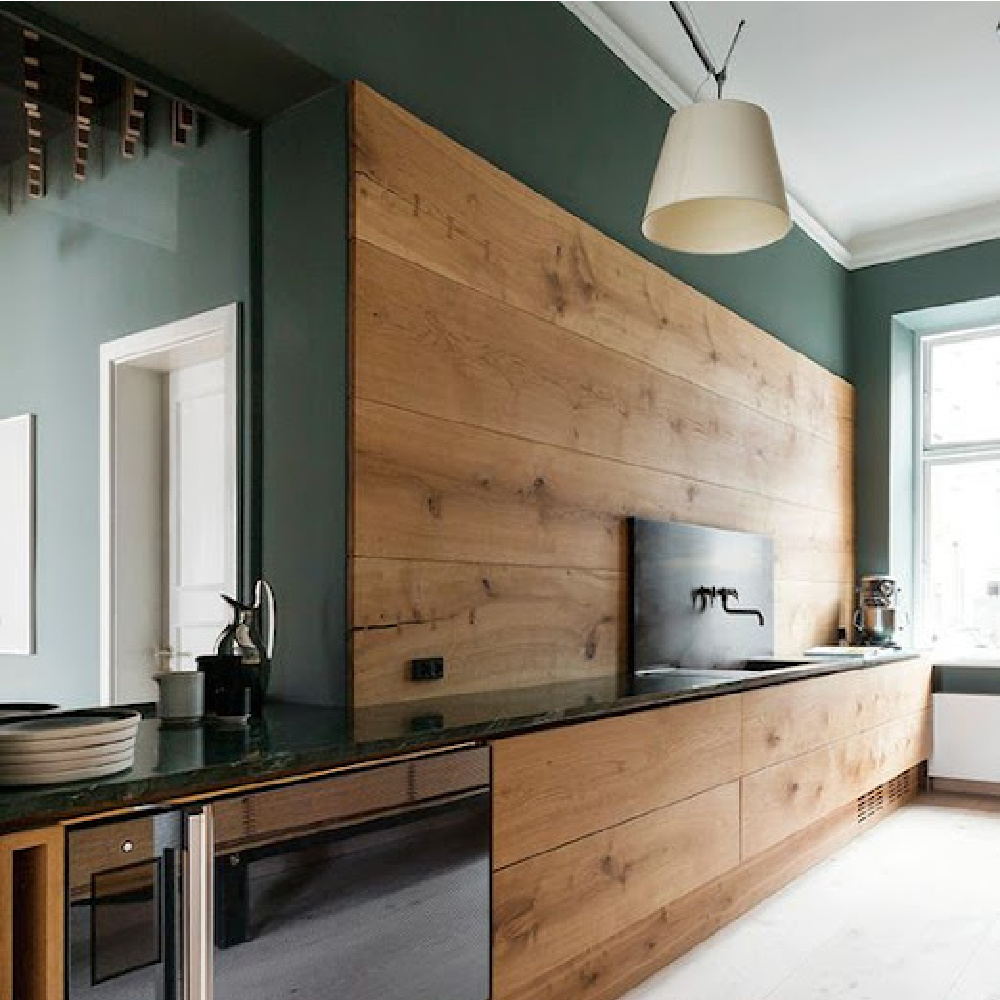 Deep and dark green walls in a rustic kitchen with wood backsplash by dinesen - Come explore Dark Green Paint, Autumnal Greens & Interior Design Inspiration!