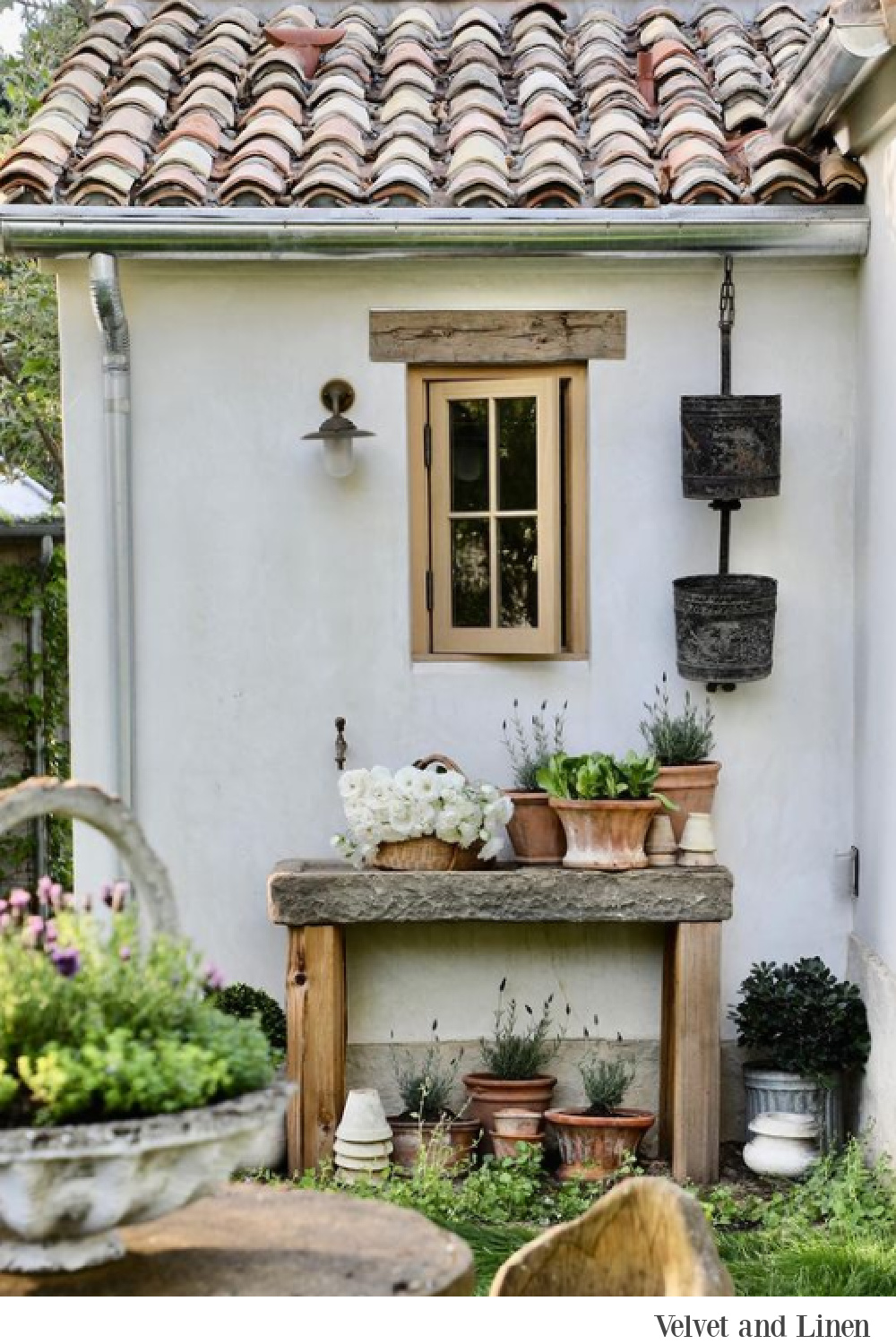French country style at Patina Farm where pots are gathered on a potting shed - Velvet and Linen.