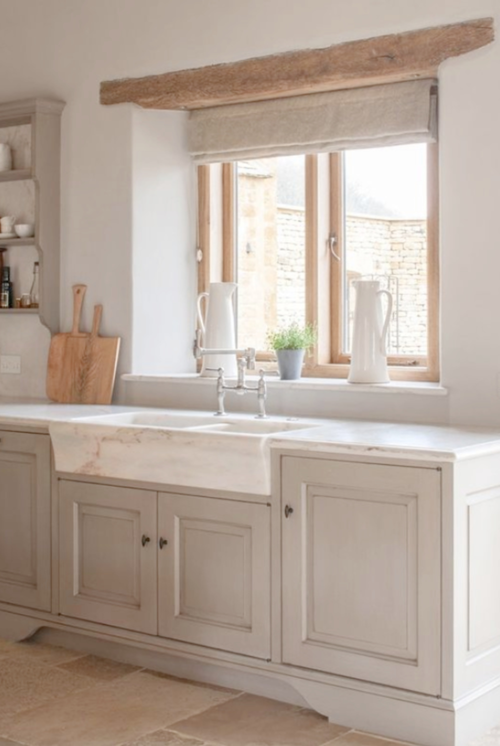 Bespoke kitchen design by Artichoke in this Old World space with Bentall marble sink, stone floor, and pale cupboards. #marblesink #bespokekitchen