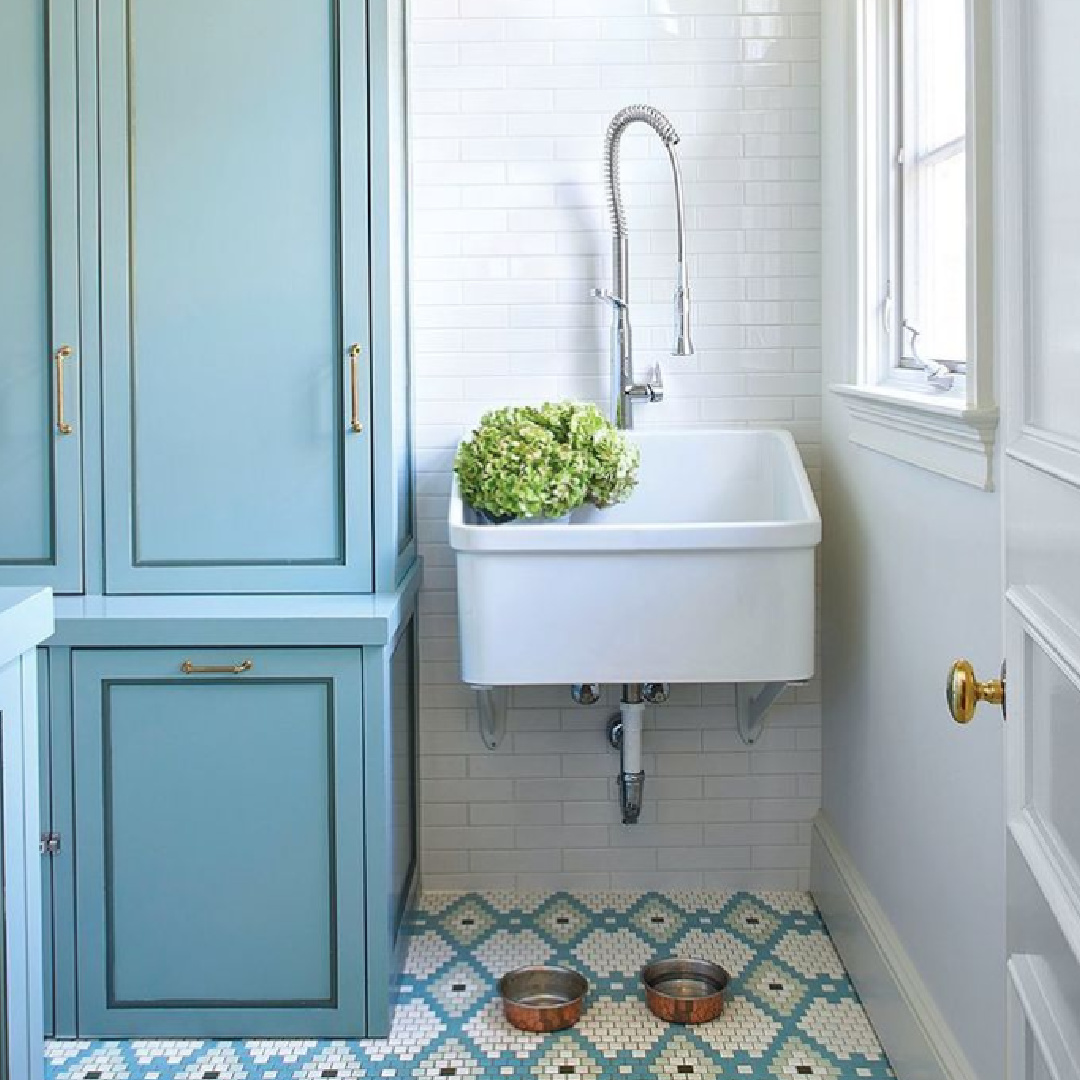 Laundry room with Swedish blue cabinets, whimsical patterned tile floor, and country sink with modern faucet - Birmingham Home & Garden. #laundryrooms #mudrooms #interiordesign
