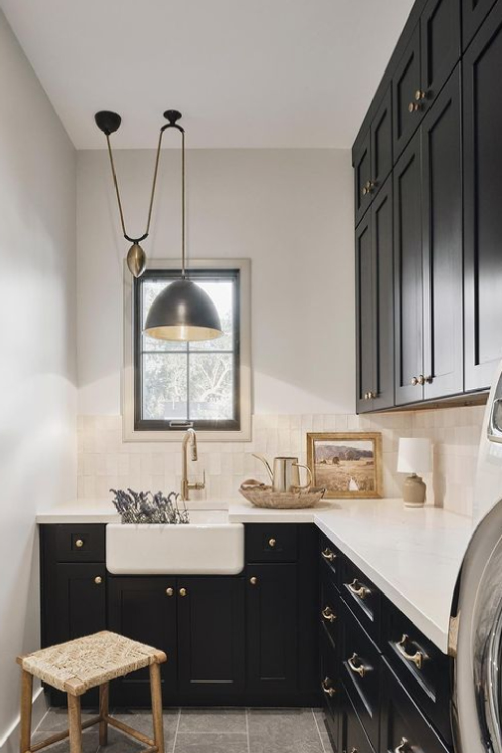 Beautiful black and white laundry room with black cabinets, Zellige tile backsplash pendant over farm sink, and white counters - @_rafterhouse_ #laundryrooms #blackcabinets
