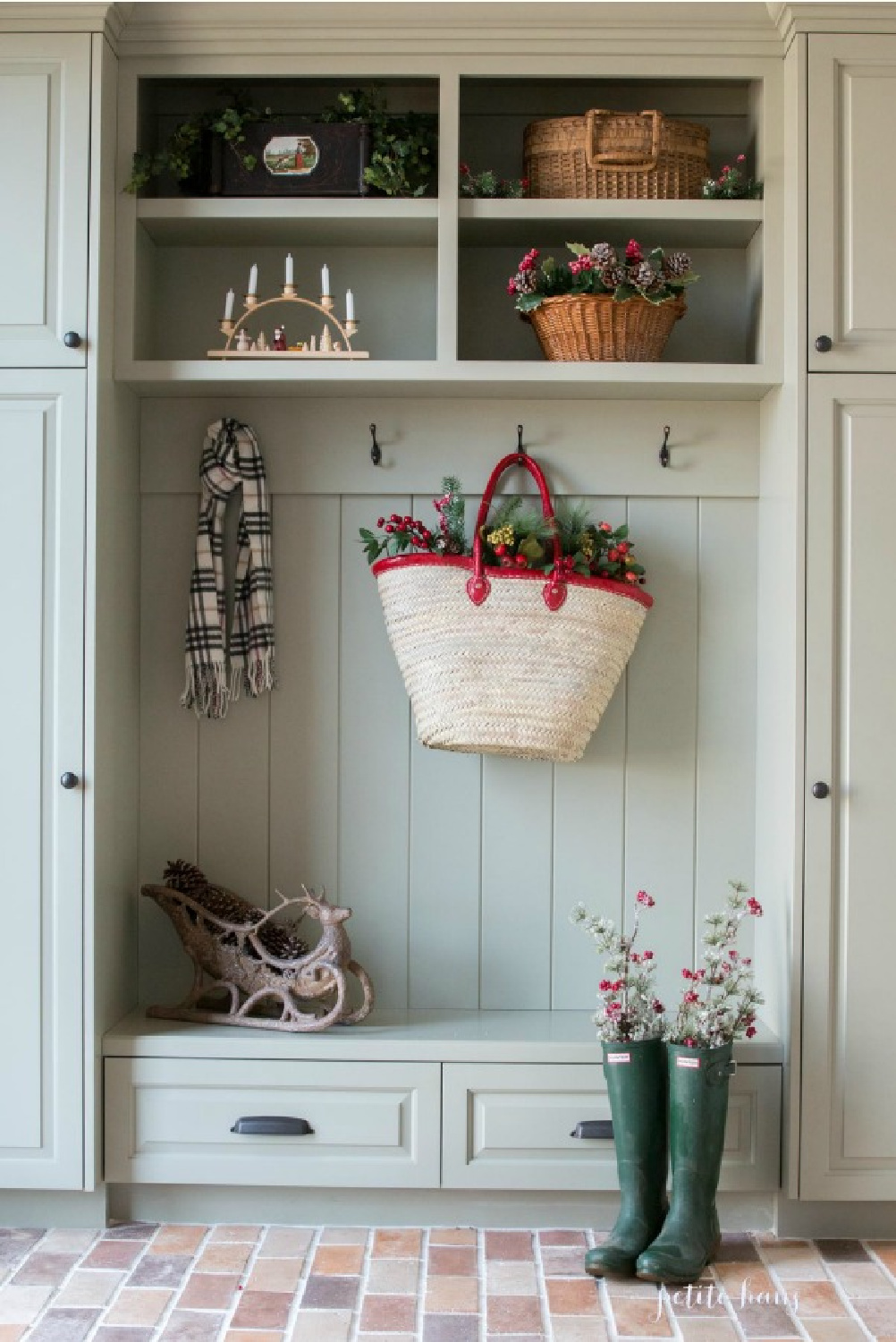 French country Christmas decor in a pale green mudroom with basket of greenery and boots - PetiteHaus. #christmasdecor #frenchcountrychristmas