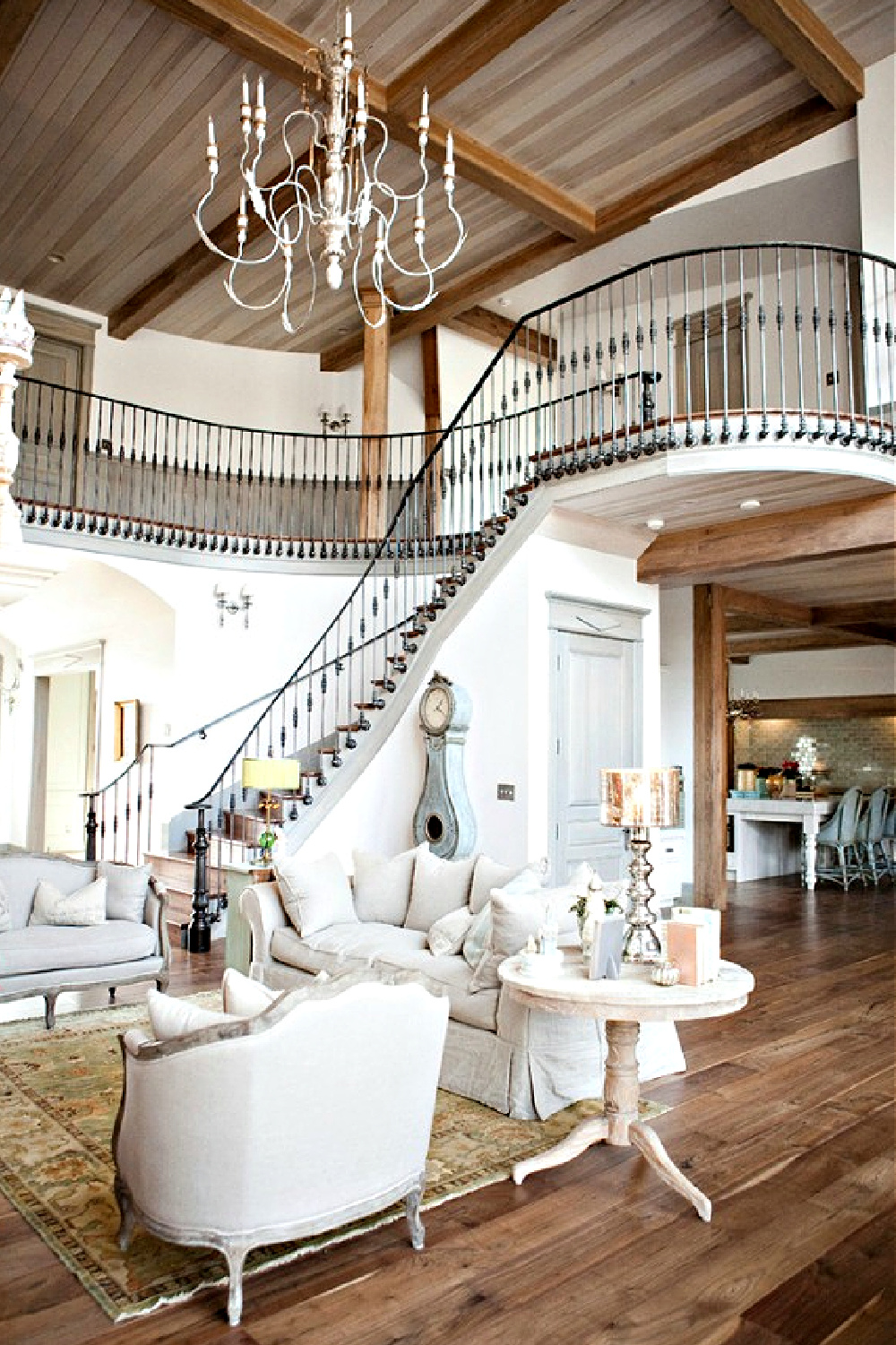 French country great room with magnificent wrought iron staircase and white decor - Desiree Ashworth. #frenchcountry #greatrooms