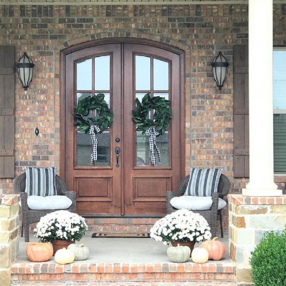 Porch with fall decor, mums, wreaths with ribbon, and pumpkins - Maven Haven. #fallporch #fallfrontdoor