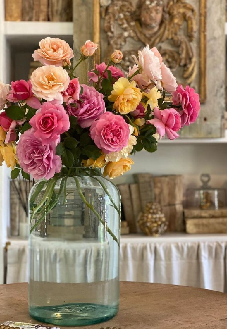 Gorgeous colorful blooming roses in a green glass jug vase in a French farmhouse inspired kitchen at Patina Farm by Brooke Giannetti. #patinafarm #frenchfarmhousekitchen #europeancountrydecor #floralarrangements #frenchcountrystyle