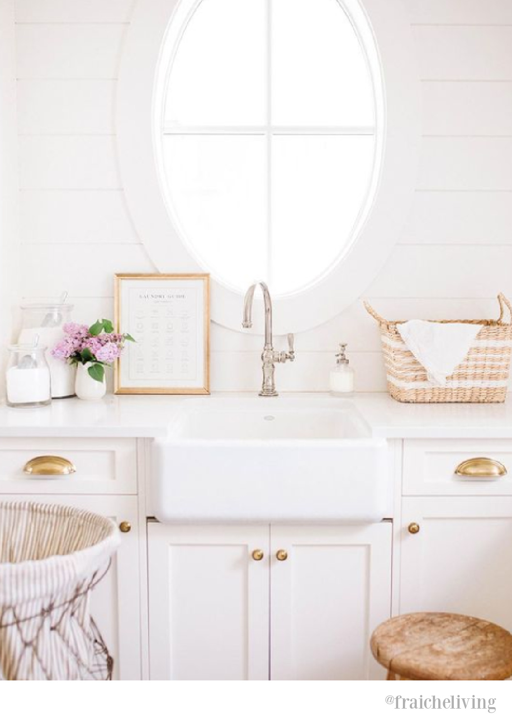 Lovely oval window over farm sink in a white country laundry room by Fraiche Living. #laundryrooms #ovalwindow #farmhouselaundryroom