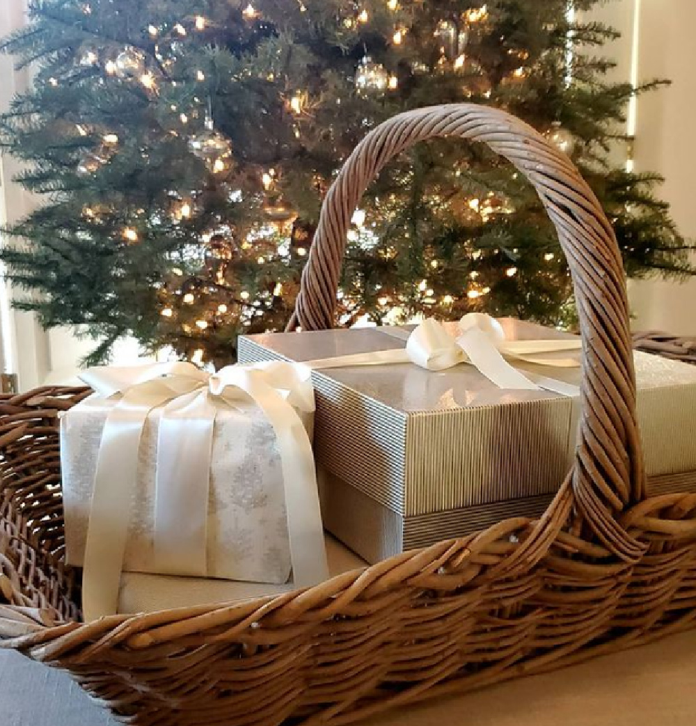 Elegant gifts tied in white ribbon in a French basket near Christmas tree - The French Nest Co Interior Design