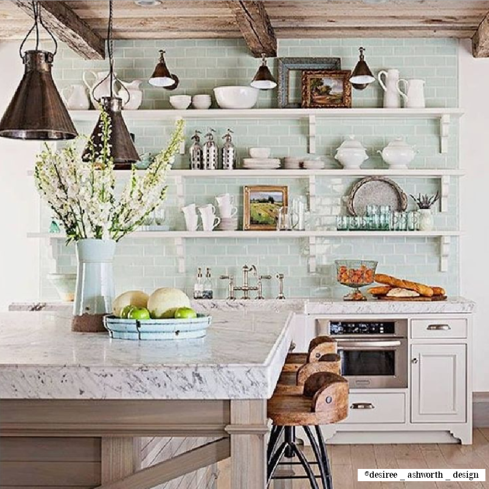 Light green accents in a rustic French farmhouse kitchen by Desiree Ashworth Design. #frenchkitchen #frenchfarmhouse #openshelves #subwaytile