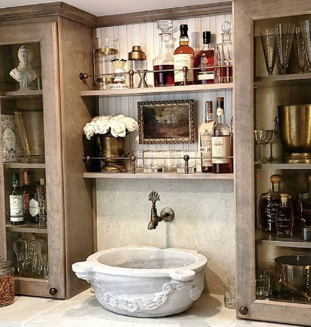 Rustic elegant French country wet bar with stone sink, wall mount faucet, and glass front cabinets - @thefrenchnestcointeriordesign
