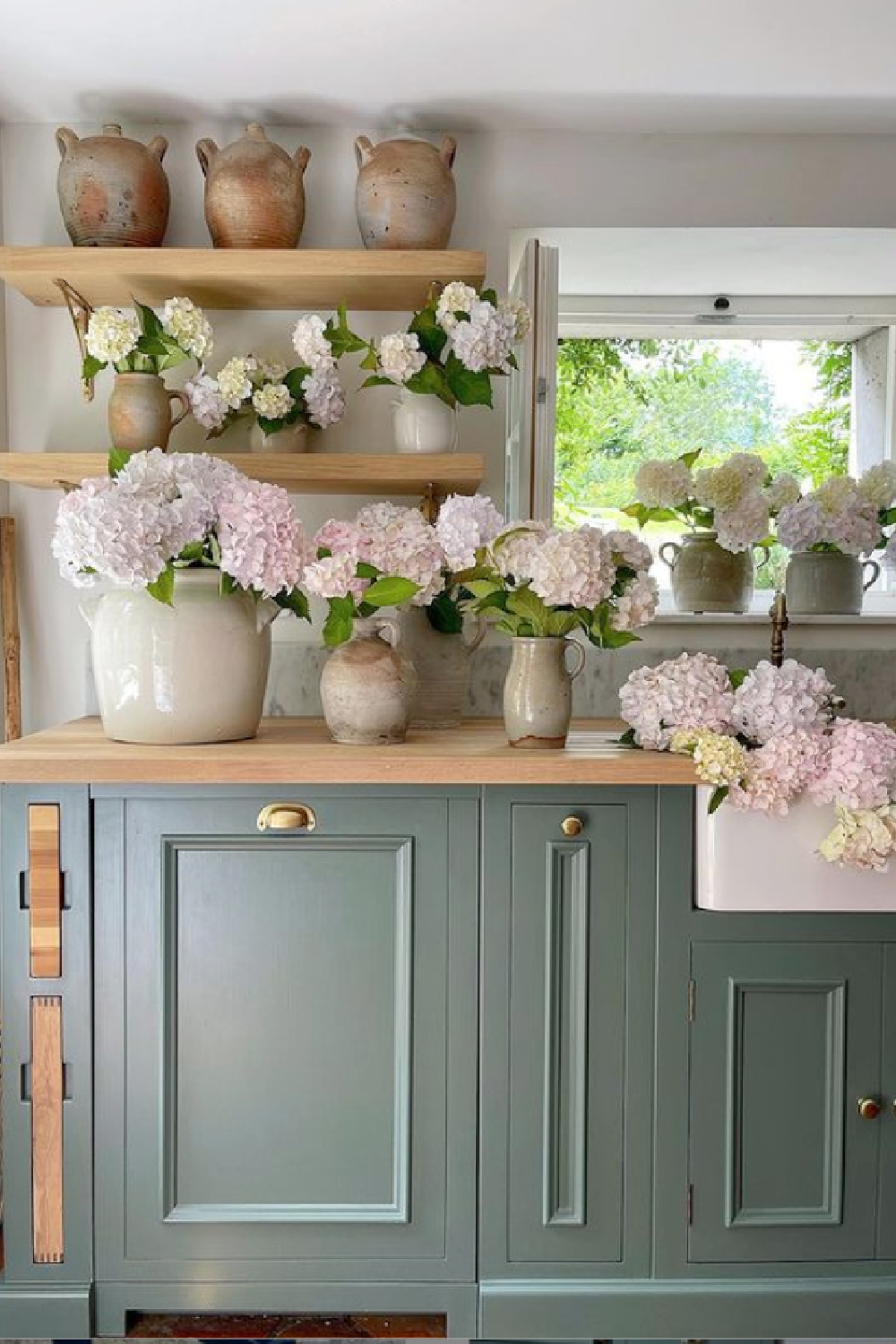 Green Smoke (Farrow & Ball) paint color on cabinets in a rustic elegant French farmhouse kitchen by Vivi et Margot. #frenchkitchen #greensmoke #paintcolors #frenchcountrykitchen