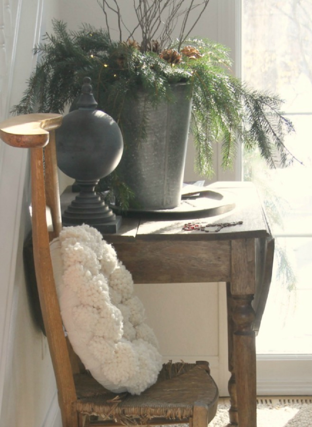Hello Lovely's holiday decor with pom pom wreath on French prayer chair with vintage table in entry. #holidaydecor #pompomwerath