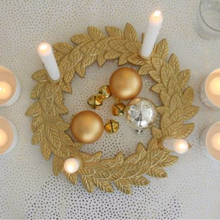 My gold advent wreath with candles lit on the table for Christmas - Hello Lovely Studio. #goldandwhite #christmasdecor #adventwreath