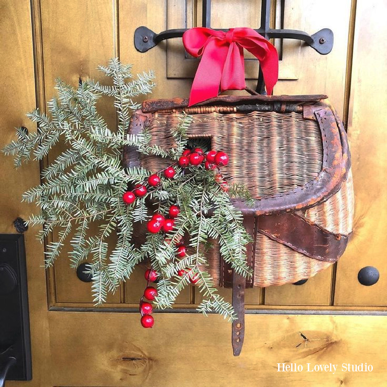 My alder front door with speakeasy with Christmas greenery and berries in vintage woven fishing basket - Hello Lovely Studio. #frontdoor #christmasdecor #holidaywreath #doordecor