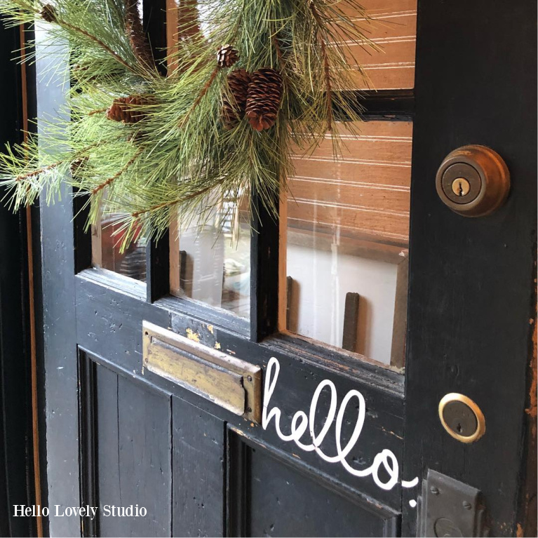 "Charming farmhouse front door painted black and handlettered with ""hello"" is decorated with Christmas wreath at Urban Farmgirl - Hello Lovely Studio. #farmhousechristmas #frontdoor #blackdoor #holidayporch"