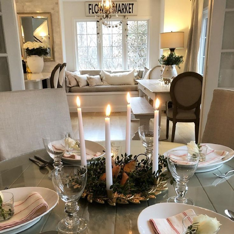 Christmas tablescape with gold advent candle wreath, white decor, and simple European country inspired design - Hello Lovely Studio. #holidaydecor #christmasdecorating #tablescape #adventwreath