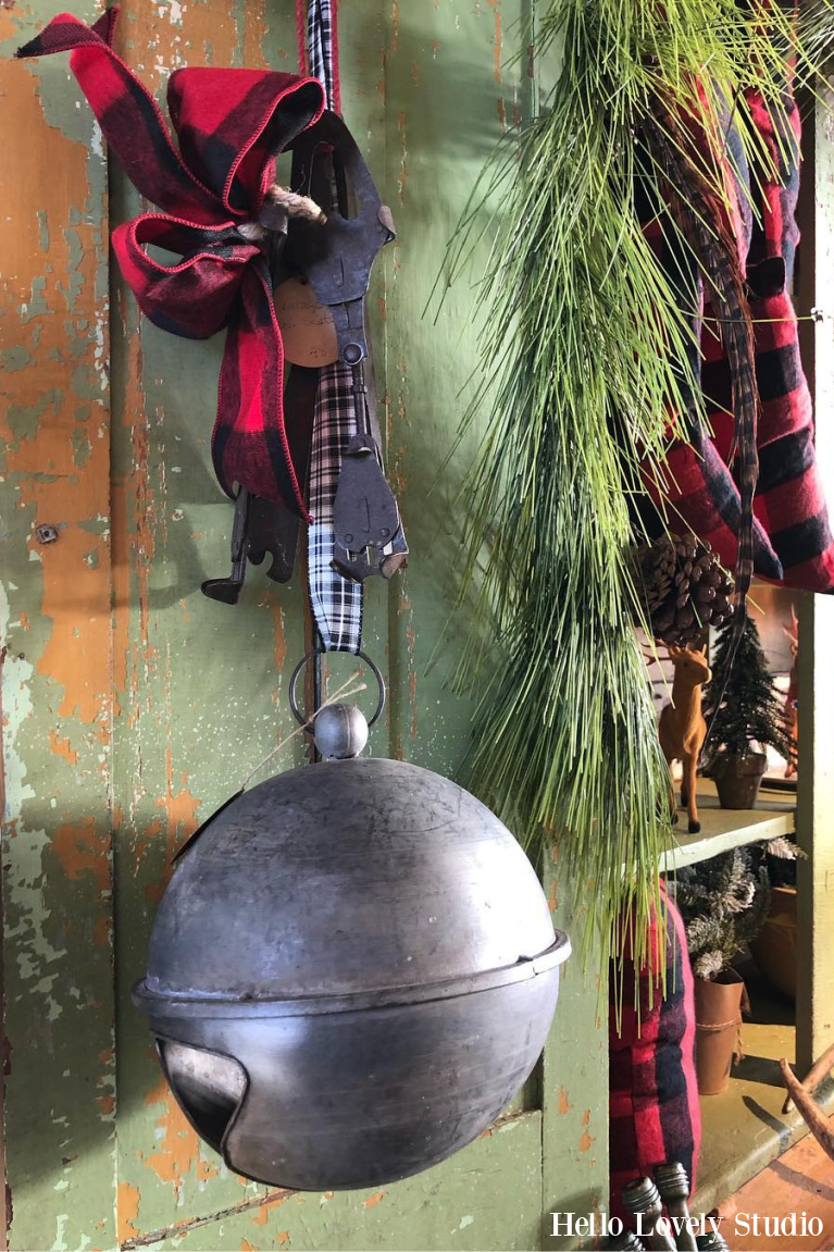 Farmhouse Christmas decor with galvanized large bell hung from ribbon on green vintage door - Hello Lovely Studio. #christmasdecor #christmasbell #farmhousechristmas #vintagechristmas #frontdoordecor