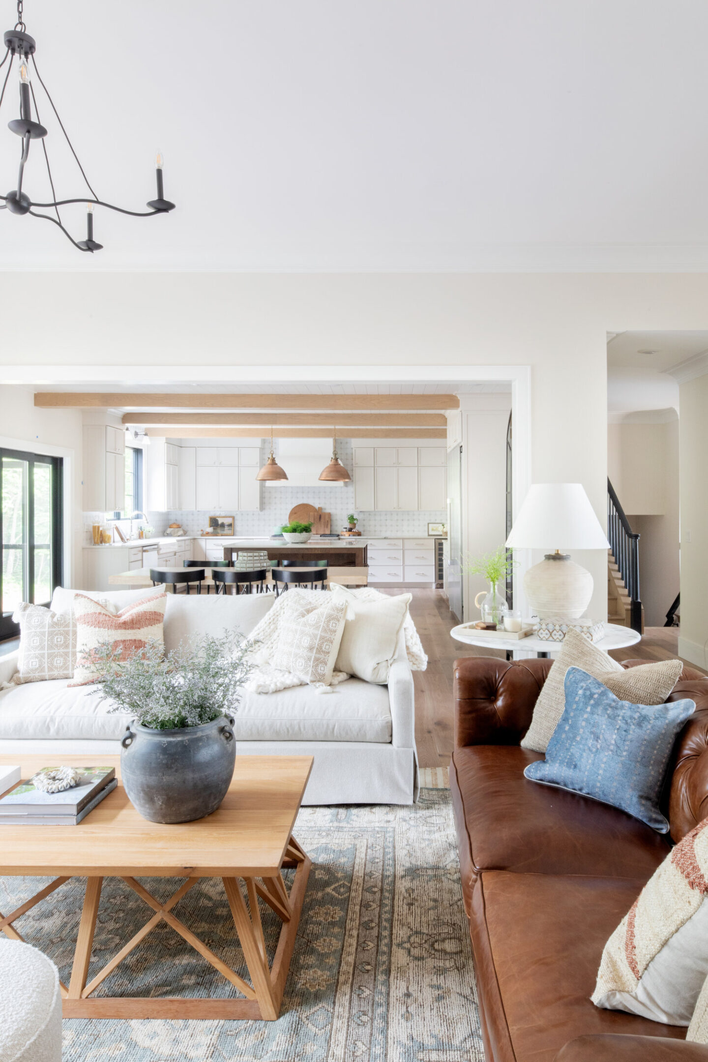 Great room with upholstered ivory sofa and tufted leather sofa - design by Bodine White; sofas by Scout & Nimble. #greatrooms