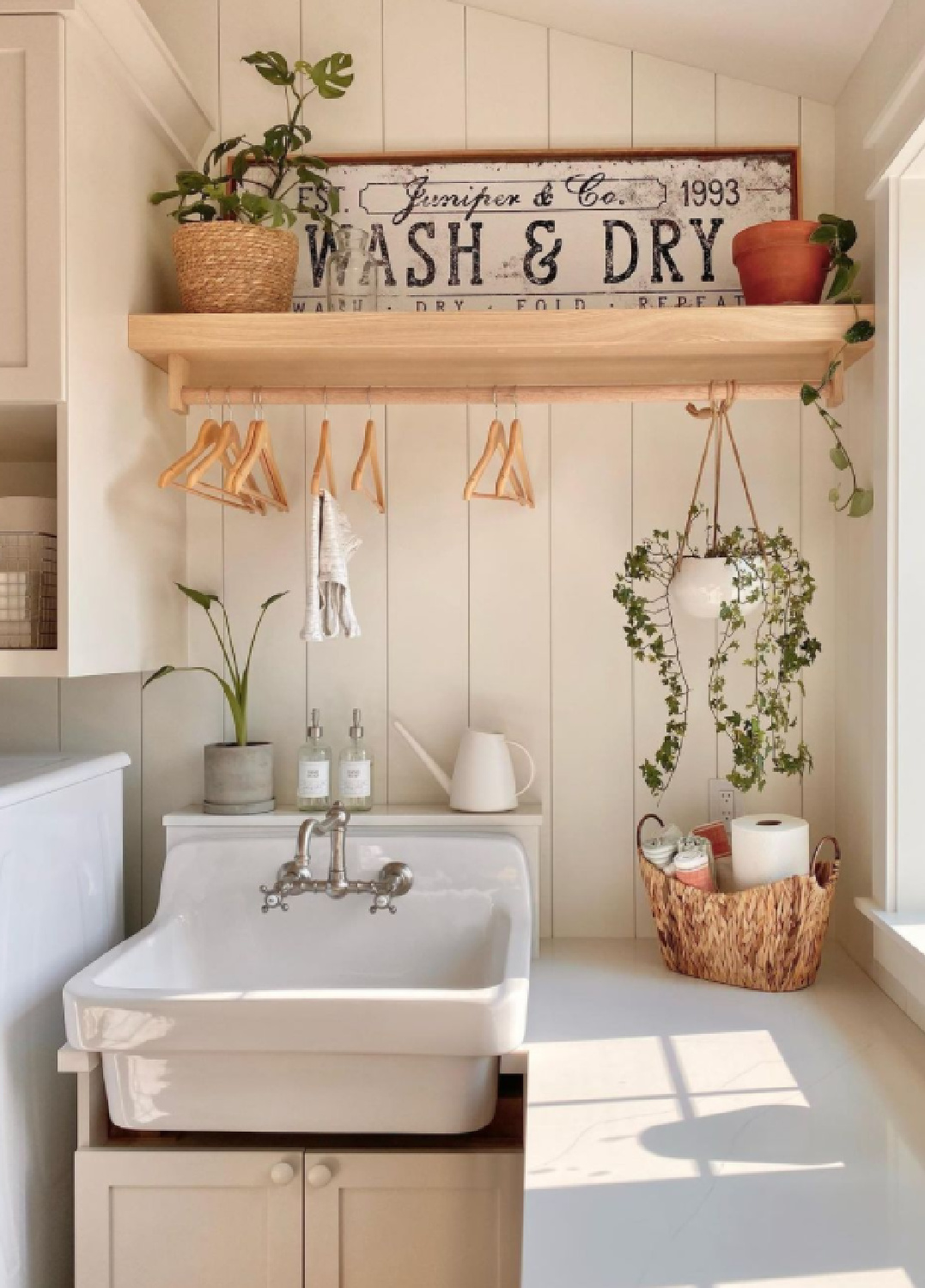 Beautiful farmhouse style country laundry room with space to hang clothing above farm sink and folding counter under window - @juniper.creek.farmhouse #farmhousestyle laundryrooms