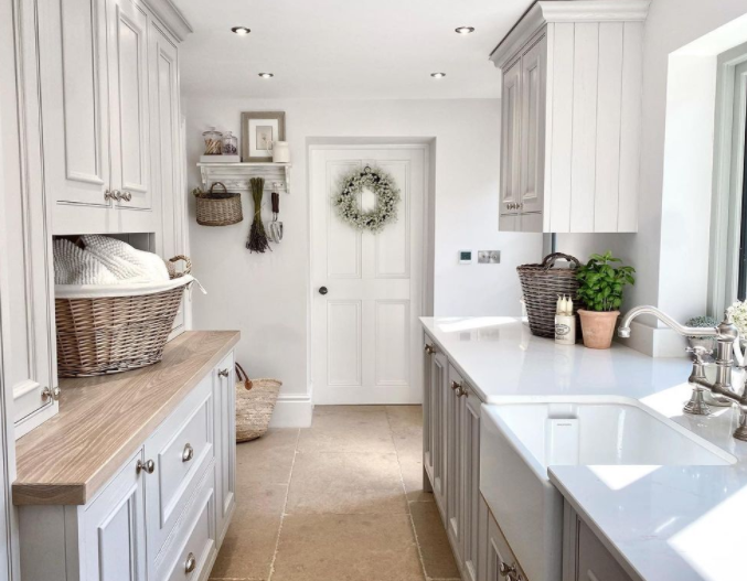 Serene laundry room with light grey cabinetry, farm sink, and galley style - Katy Harwood. #laundryrooms #farmhouselaundryroom