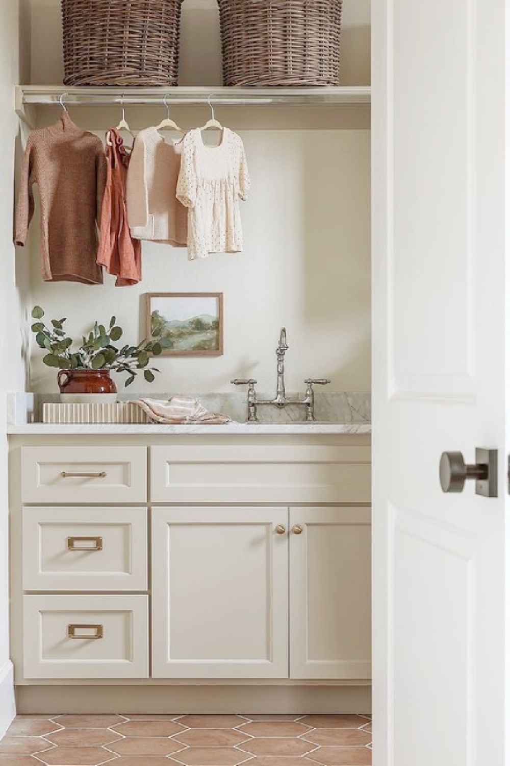 Sophisticated laundry room with putty cabinets, terracotta hex tile, and bridge faucet - Kelsey Leigh Design Co. #laundryrooms #interiordesign