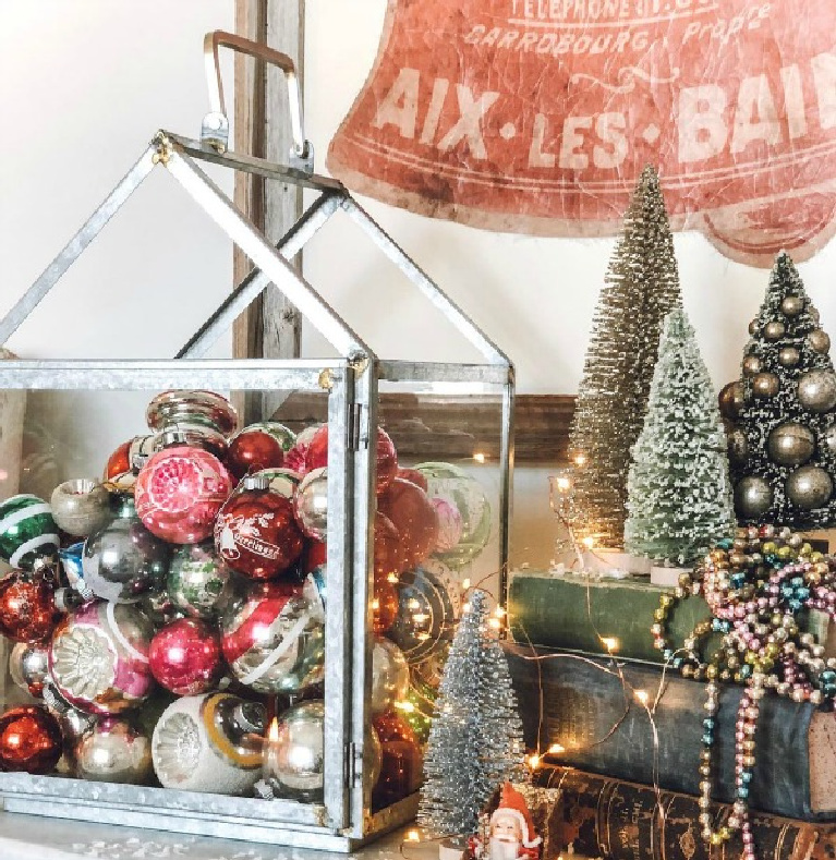 Vintage ornaments in glass hurricane lantern for vintage Christmas charm from Le Cultivateur. Find more simple Christmas decor ideas on Hello Lovely Studio.