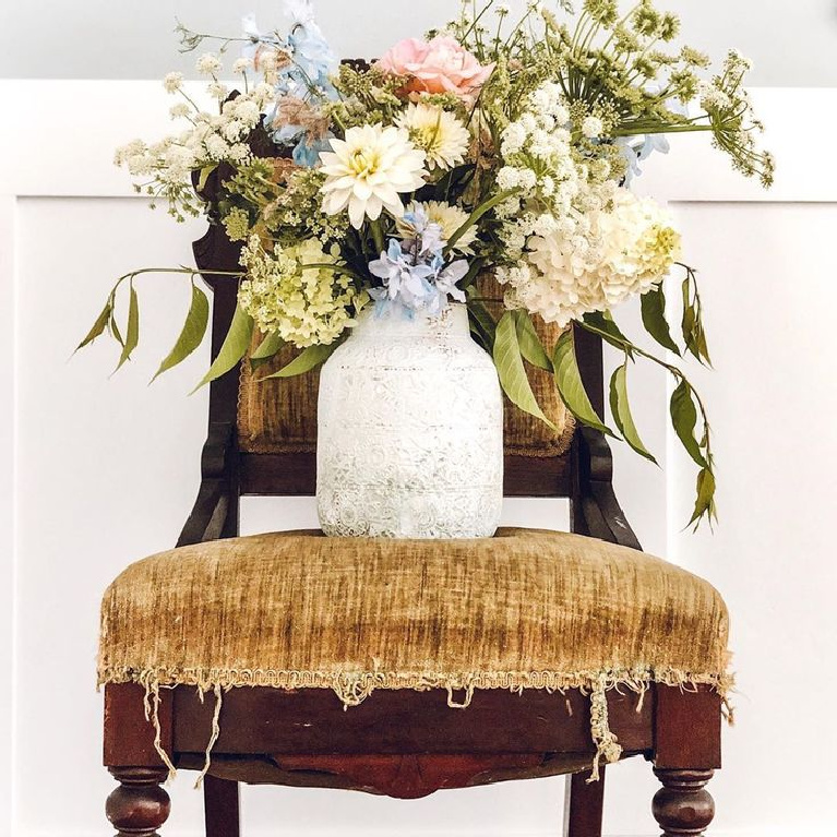 Romantic French farmhouse blooms in rustic vase upon vintage tattered velvet chair - Le Cultivateur.