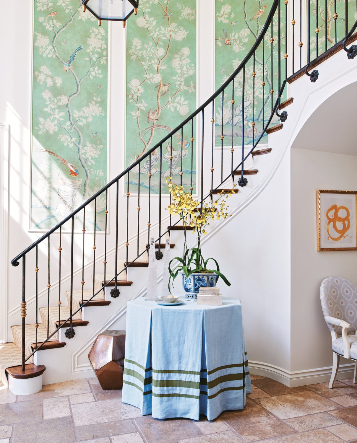 Mark Sikes designed entry with wrought iron staircase and skirted round table. #traditionalstyle #entry #interiordesign