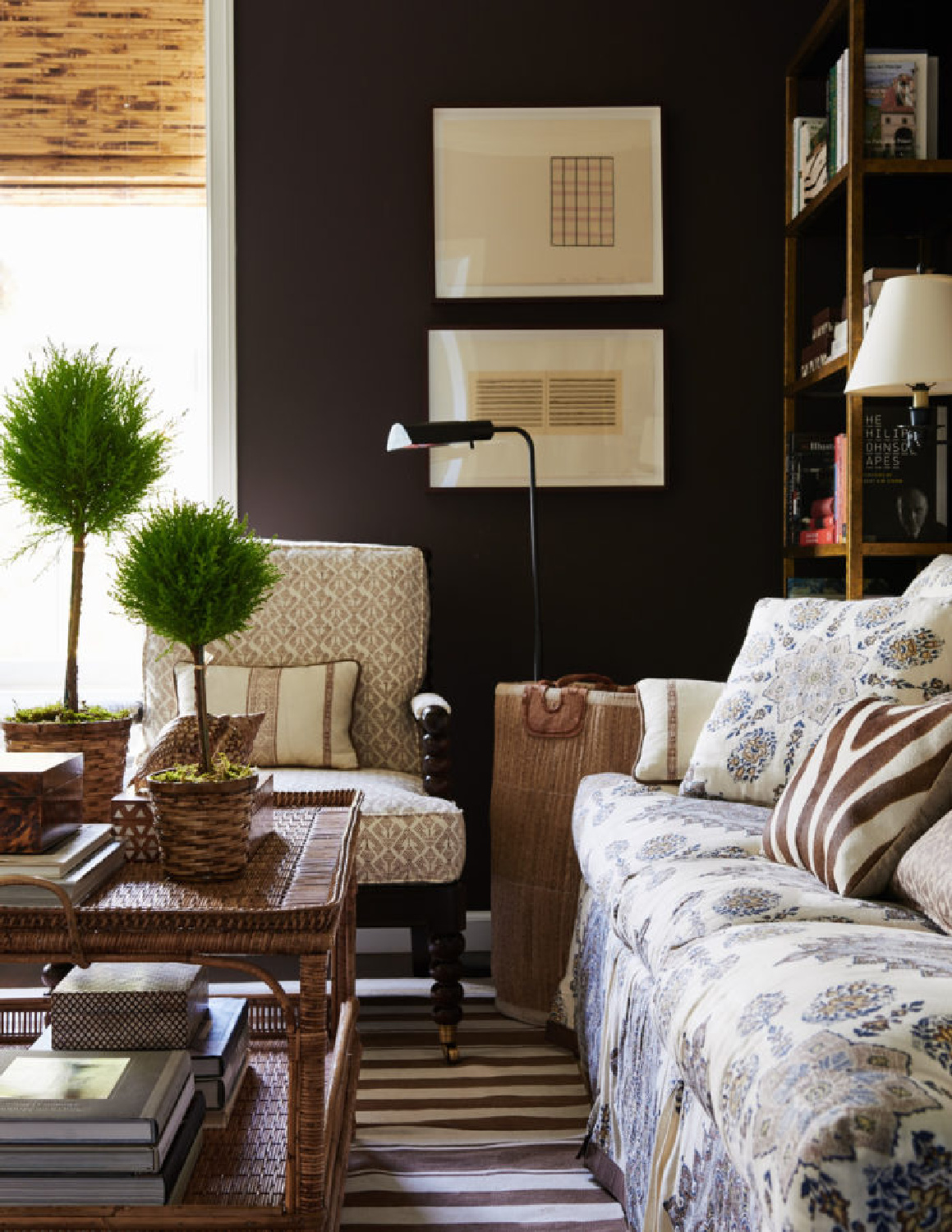 Dramatic black wall in a living space with traditional design by Mark Sikes.
