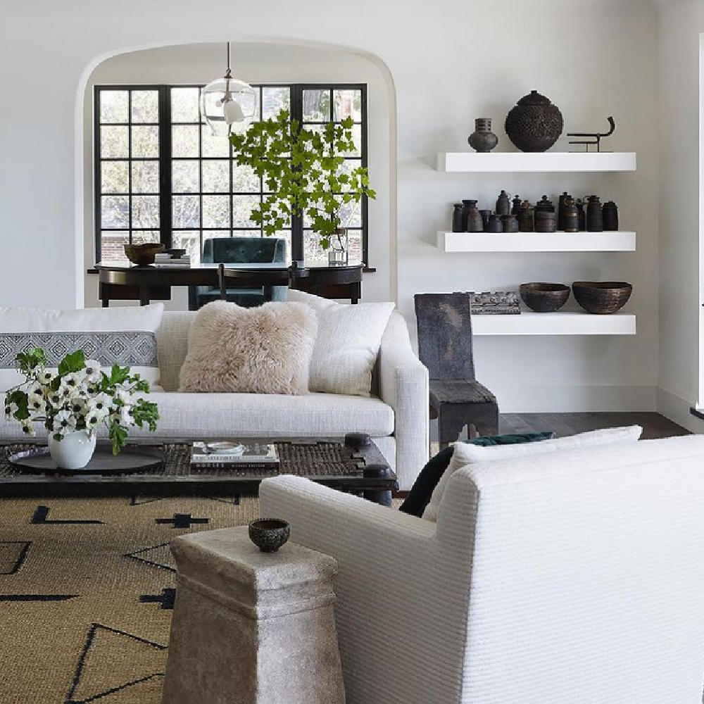 Exquisite modern rustic living room by Michael del Piero with floating shelves, black pottery, and neutral furnishings. #mdpgooddesign #modernrustic #interiordesign