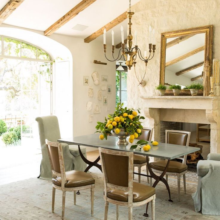 Patina Farm dining room with lemons on table, antique French chairs, and French limestone fireplace. Giannetti Home.
