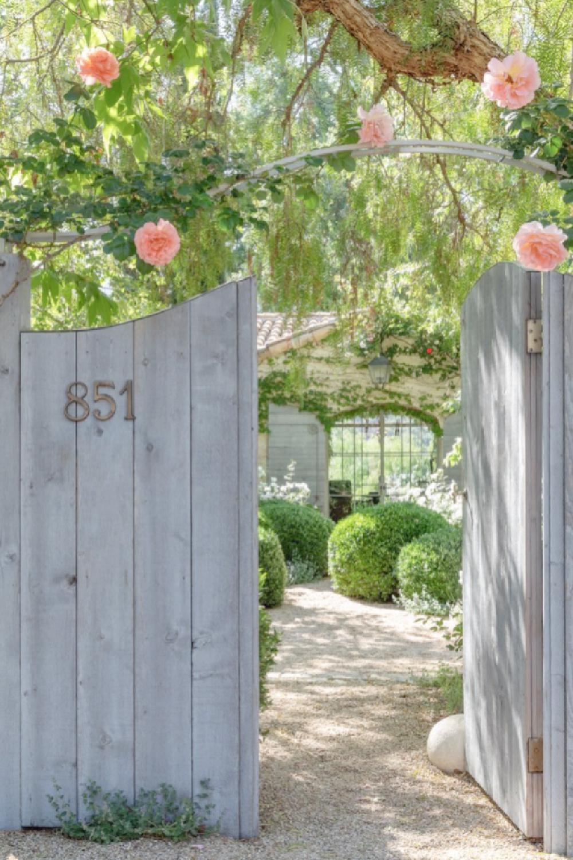 Patina Farm entrance gate rose arbor and home exterior - Brooke Giannetti. #patinafarm #frenchfarmhouse #farmhousegarden