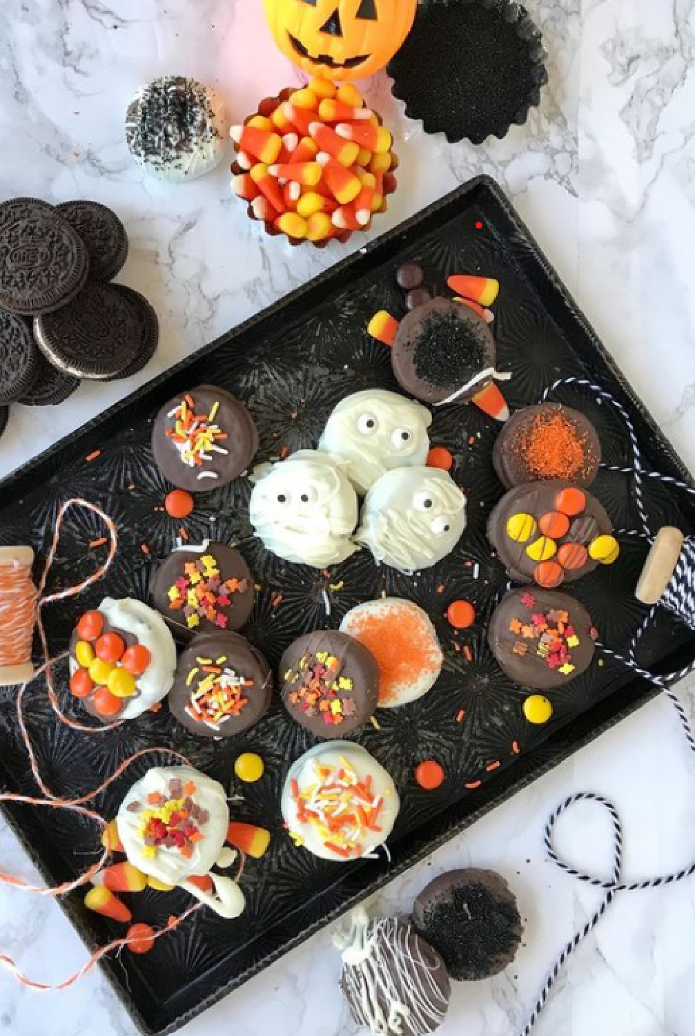 Halloween goodies and treats on a black tray with orange baker's twine - PineconesandAcorns. #halloween #tablescape #sweetsboard