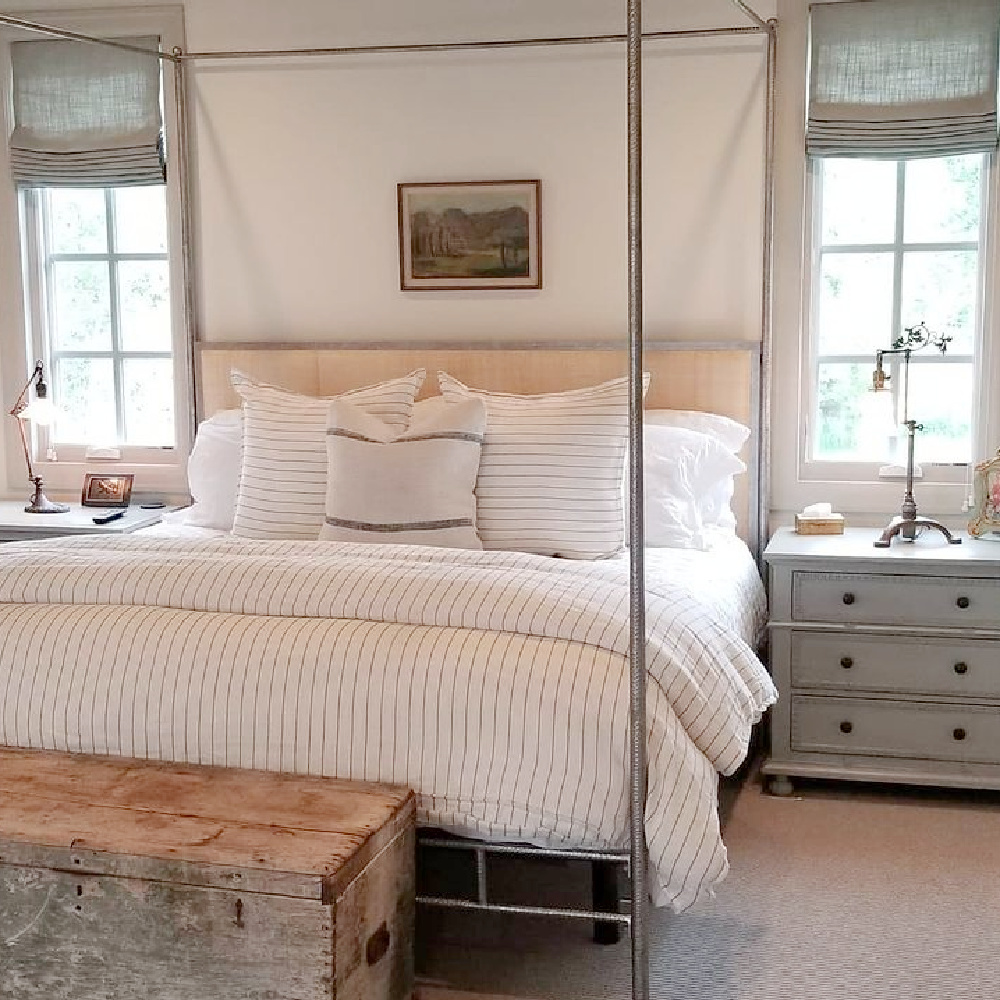 Rustic modern French bedroom with linen roman blinds, poster bed, raw wood trunk, and sumptuous bedding - design by @beljarhome. #serenedecor #modernfrench #europeancountry #bedroomdecor