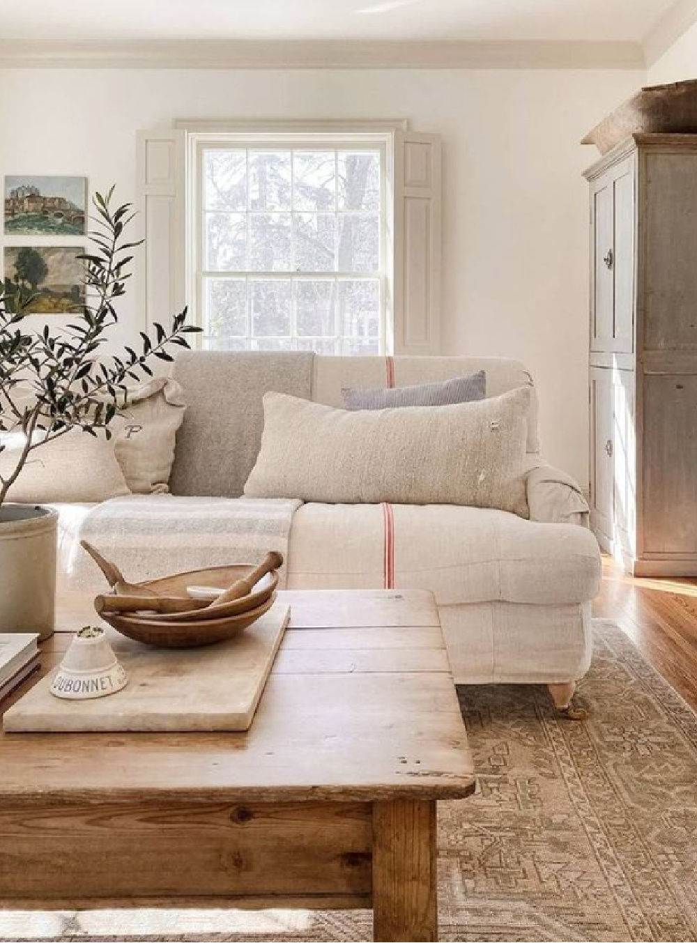 Understated and serene neutral interior with nubby linen sofa and putty shutters - @burtsbrisplease. #europeancountry #neutraldecor #belgianstyle