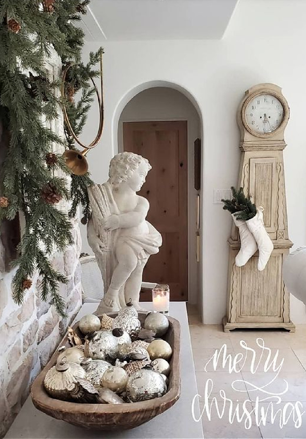 Breathtaking French country Christmas decor with white stockings hung from Swedish clock, cherub, wreath, and dough bowl with silver balls - The French Nest Co Interior Design